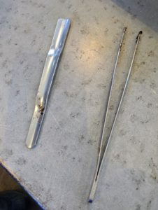 These tools are great for transplanting seedlings. The tool on the right is a pair of tweezers. The one on the left is from Johnny's Selected Seeds. It's called a widger. It has a convex stainless steel blade that delicately separates the tiny plants.