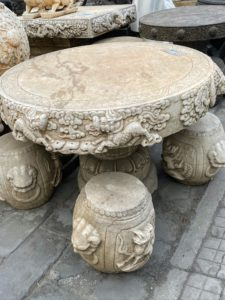 Here was an ornate table with four stone stools.