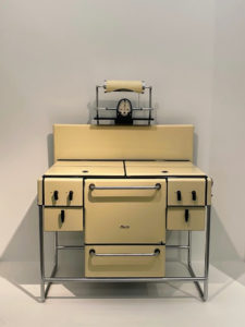 This is a Magic Chef stove, manufactured by the American Standard Stove Co. It is an American art deco stove, oven, and griddle made in 1936. It is porcelain over cast iron with chrome steel supports and handles for the oven and under storage.