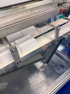 These machines cut the non-woven fabric that is used to make cleansing wipes. The machines cut, fold, and stack the wipes for packaging.
