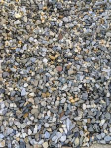 I like to use a small-size natural colored gravel.
