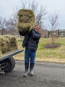 Meanwhile, nearby, Fernando carries a bale of hay, also made right here at the farm, and drops it strategically where rain runoff may cause damage to the lawns and garden beds. We're expecting some rain this week.