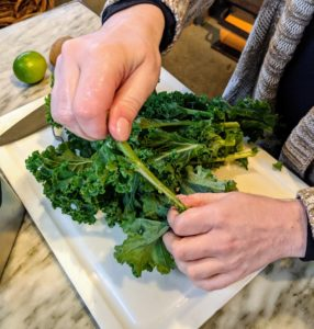 The Kiwi-Lime Smoothie starts with kale. Shqipe strips the kale from the stems.