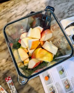 Once everything is cut, Shqipe transfers the kale, kiwi, and apple into the blender.