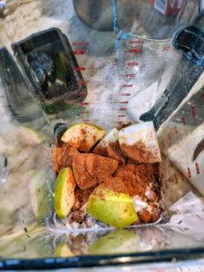 Shqipe then adds the coconut milk powder, pears, cocoa powder, and liquid of choice to the blender.
