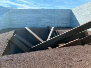 """This is called """"Collapse"""" (1967/2016) by Michael Heizer, a land artist specializing in large-scale and site-specific sculptures. This artwork consists of 15 heavy beams of rusted steel that appear to have been tossed into a deep pit lined with vertical walls."""