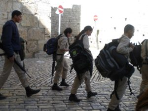Young Israeli Naval soldiers on a group trip to see Jerusalem - the female soldiers carry heavy bags and weapons, too.