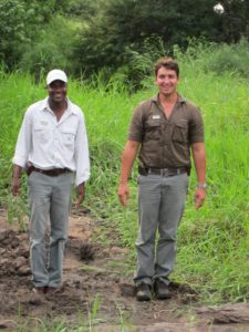Thembe and Marlon standing in elephant footprints in the dried mud of a small river.  They carried guides to birds, mammals, insects, trees, etc. with them to back up their sightings and their findings.