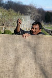 Chhewang is using a large needle to sew the burlap onto the frame.