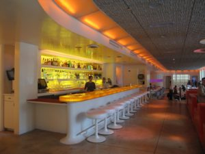 This bar features a translucent amber resin bar top, lit from beneath with white neon.
