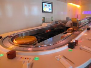 This oval-shaped sushi bar has a conveyor belt that delivers the freshly prepared sushi.  Above the sushi bar, a large, screen shows non-stop video clips.