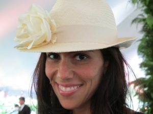 Rory Tahari, wife of Elie Tahari, the famous designer, wore a fedora straw hat with one white rose - very chic.