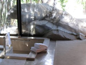 The master bathroom, equipped with a sunken tub, has a floor-to-ceiling view of the rocks and bamboo outside.