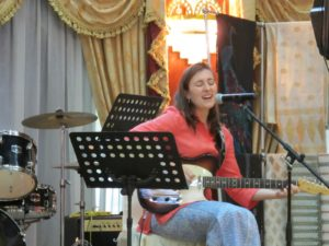 Here is Sophie singing at the tea party.  When I mentioned to the Queen that Sophie sang, she generously requested that Sophie do so.  Sophie borrowed an electric guitar from the combo that was playing during the tea party.