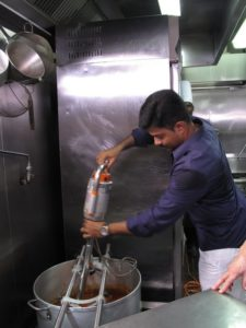 After adding the spices and the coconut milk, Visvanaath uses a large immersion blender to combine the ingredients into a smooth mix.