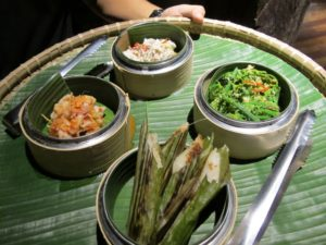 Some delicious appetizers served at dinner, including prawns, glutenous rice grilled in bamboo leaves, and sautéed local ferns.