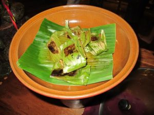 Chicken was wrapped in banana leaves and grilled.