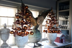 Copper tinsel trees are decorated with copper balls and pine cones in the servery.