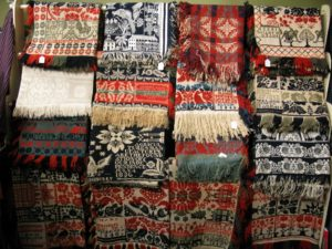 This is a rack of finely woven overshot coverlets.