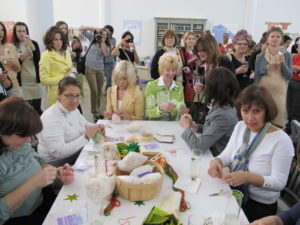 A busy group finishes their tomato pincushions.