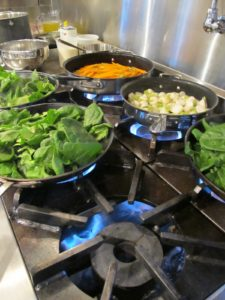 My professional range makes cooking for twenty easy - fresh spinach from the cold house - sauteeing alongside turnips and carrots.