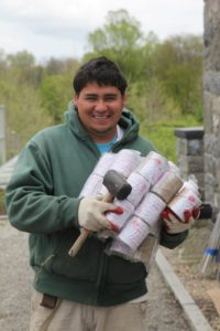 Wilmer emerges from the greenhouse - this time with many packages of twine.