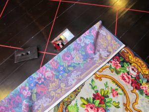 Beneath a colorful floor covering is a peep hole, which looks down into the main foyer.  The bride-to-be would use this to catch a glimpse of potential suitors who came to call.