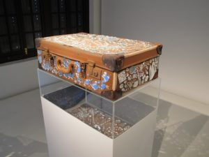 A suitcase highly decorated with mirrors.