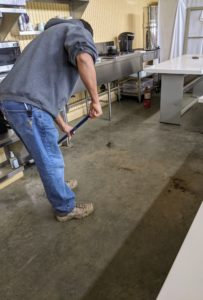 First, Carlos thoroughly sweeps the concrete floor of any dust and dirt. Because this area can get dusty, Carlos works from the bottom up, so all the eating surfaces are cleaned last.