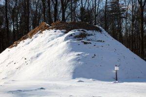 A rather large mound of compost covered with snow.