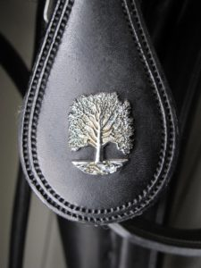 The harness decoration is nickeled brass - the tree is the symbol of the farm.  All of the harnesses are made by Freedman in Canada.  www.freedmanharness.com