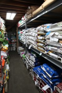 Floor to ceiling is stacked with sacks of feed.