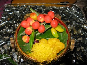 The yellow are extruded treads of sweetened egg yolk served with Thai fruits.