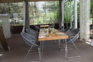 The dining room is open on two sides and is furnished with contemporary chairs and tables.