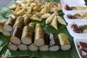 A variety healthy snacks, including glutinous rice rolled in bamboo leaf called lemang.  The triangular shaped ones are called ketupat palas.