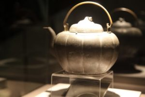 This is the melon-shaped Lucky Tea Pot.  During WWII, a man bent over to pick up this teapot and in doing so, dodged a shrapnel that whizzed just inches from his head.