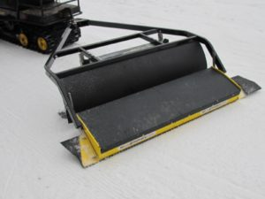 This contraption - a SNO-MASTER 48 - is hitched onto the back of a Ski-Doo or a Kawasaki - it can be weighted down with a cinder block or two on top.  It compacts and corduroys trails.