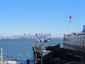 The tip of Manhattan lies off the bow of the ferry.
