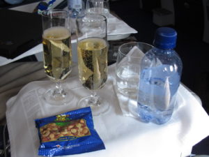 South African Airways offers good service and nice wines in Business Class.  There are also reclining beds for the long trip.