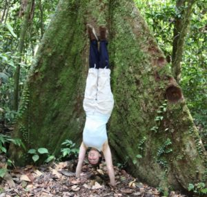 Yogini Sophie doing a handstand on the soft jungle floor