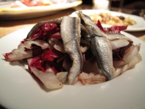 Fresh white anchovies served on a bed of dressed radicchio.