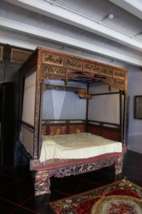 This is a sumptuously carved, lacquered, and gilded canopied wedding bed from 19th-century Penang.
