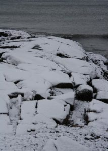 Shore rocks and their snow quilt