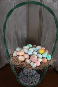 An antique beaded basket filled with straw and assorted blown and dyed eggs from years past.