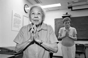 Margaret King, age 97, stands with her hands in prayer position in yoga class.