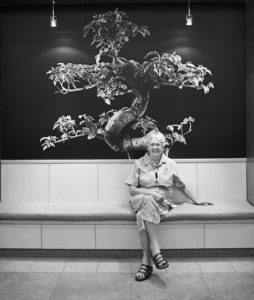 Beatrice Dryer sits in the lobby of the Martha Stewart Center for living at Mount Sinai Medical Center. Behind her, a photograph of a bonsai tree, a symbol of longevity, strength, and beauty. Photograph by John Huba