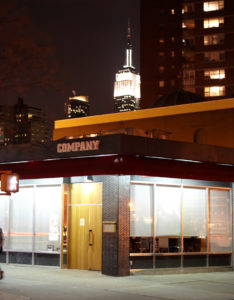The exterior of Co. with the Empire State Building shining proudly in the background.