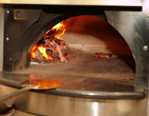 The oven at Co. is a gas-fired Earthstone oven.  Flavorful hard wood is also burned to aromatize the pies.