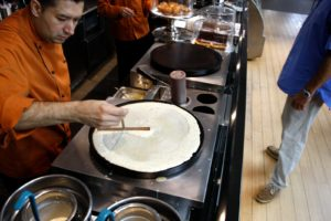 Crepes being made on a crepe griddle - they're filled in a variety of ways.
