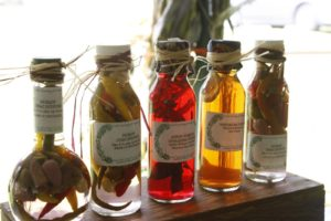 Bottles of pickled chile peppers, lemon verbena - opal basil - margoram rice vinegar, and nasturtium blossom rice vinegar